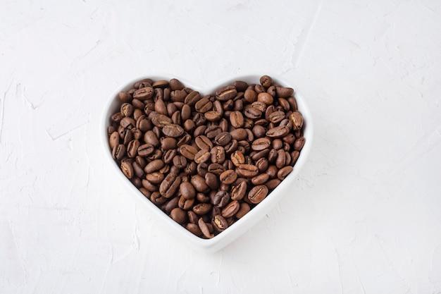 흰색 바탕에 컵 마음에 커피 콩