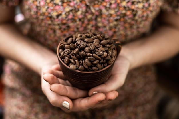 Кофейные зерна в чашке в женских руках на коричневом фоне.