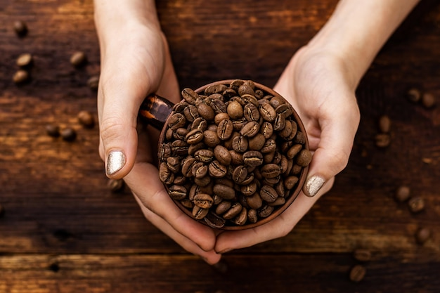 茶色の背景に女性の手でカップのコーヒー豆。