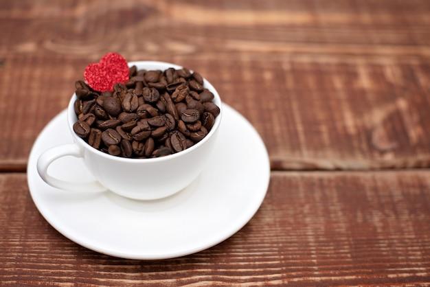 Кофейные зерна в чашке на деревянном фоне. мягкий выборочный фокус. скопируйте пространство.