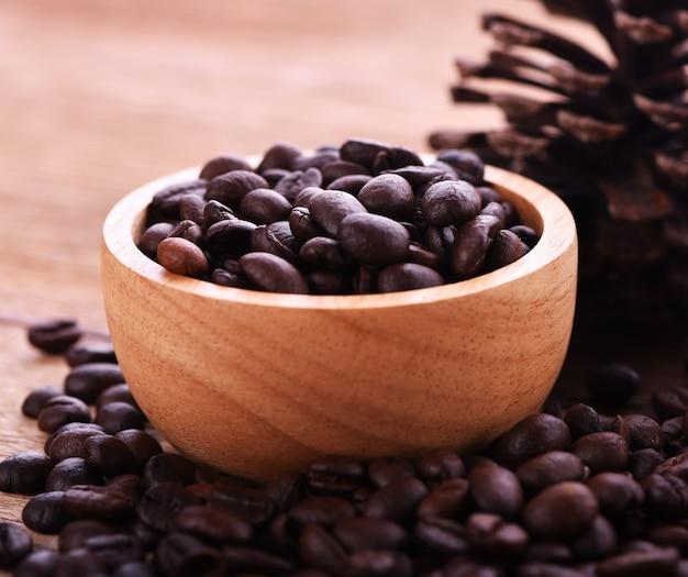 カップの木の背景のコーヒー豆