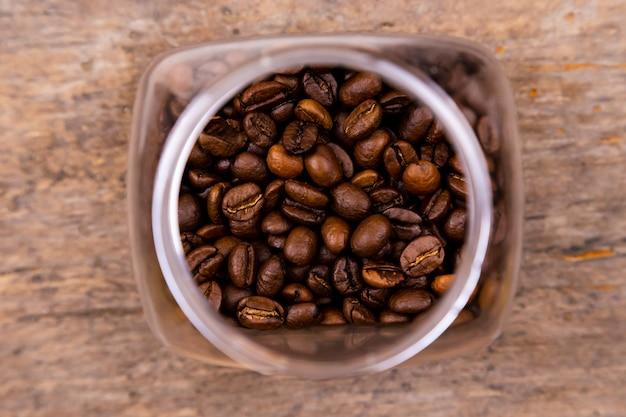Кофе в зернах в стеклянной банке на деревянном фоне, вид сверху