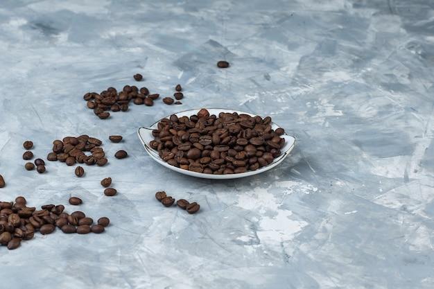灰色の石膏の背景の上のプレートのコーヒー豆。ハイアングルビュー。