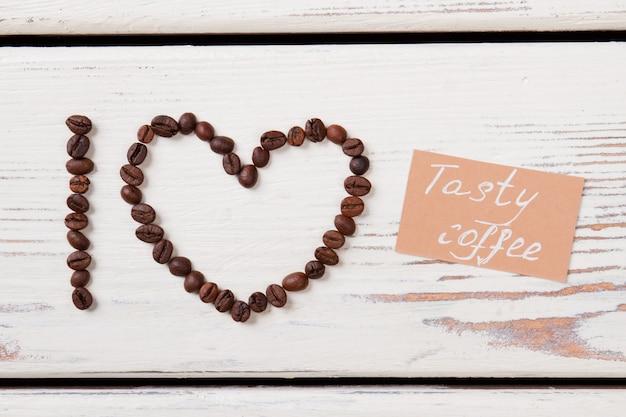 Кофейные зерна в форме сердца и i письмо. любитель вкусного кофе. белая деревянная поверхность.
