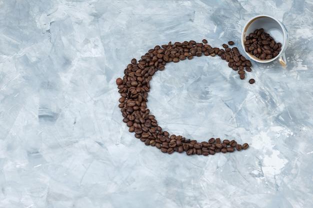 灰色の漆喰の背景に白いカップのコーヒー豆。上面図。