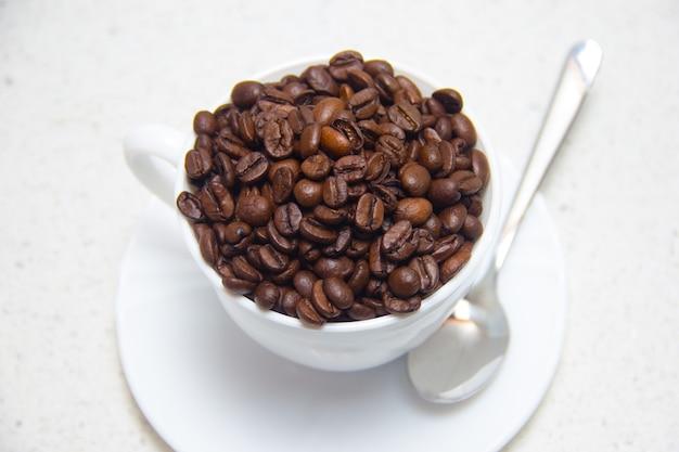 흰색 컵에 커피 콩입니다. 커피의 준비. 밝은 배경에