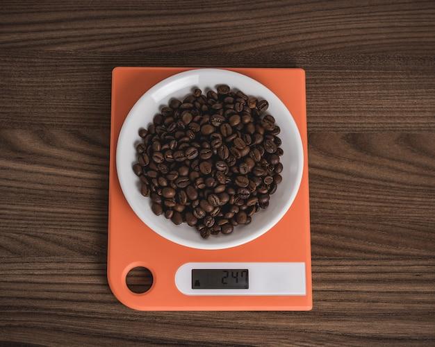 Кофейные зерна в белой тарелке на оранжевых весах