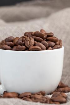飲み物用の全体の形のコーヒー豆、カップに入った芳香性のコーヒー豆、マグカップでおいしいコーヒーを作るためのコーヒー豆