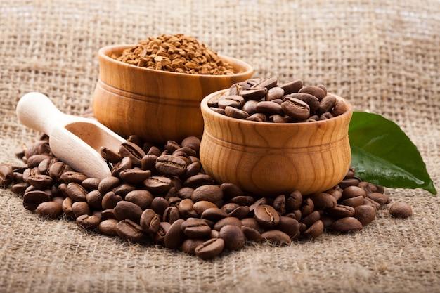 삼 베 배경에 나무 그릇에 커피 콩