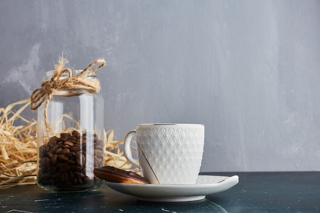 Кофейные зерна в деревянной чашке в стеклянной банке.