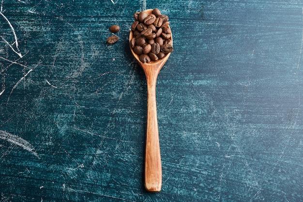 Кофейные зерна в деревянной ложке.