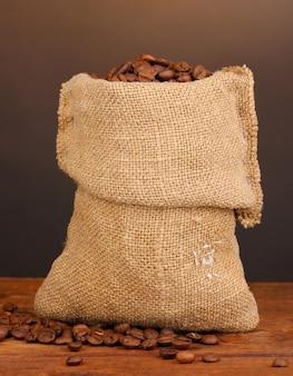 Кофейные зерна в сумке на столе на темноте
