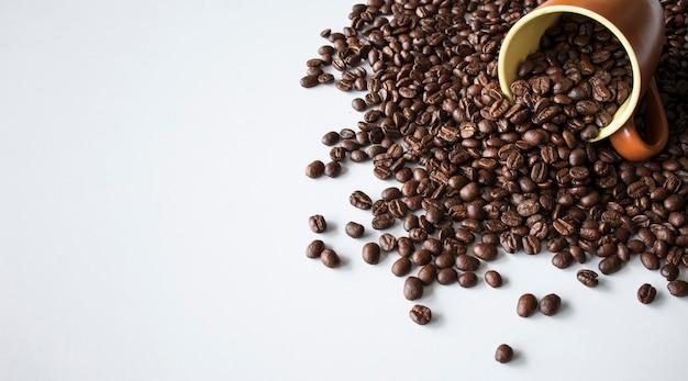 Кофейные зерна в коричневом стекле на фоне белого стола. вид сверху. место для текста