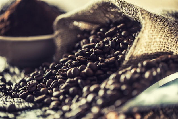 古い木製のテーブルの黄麻布の袋のコーヒー豆。