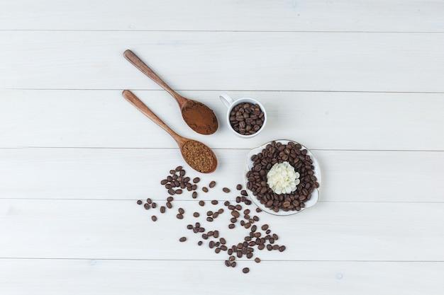 挽いたコーヒーとカップとプレートのコーヒー豆、木製の背景に花の上面図