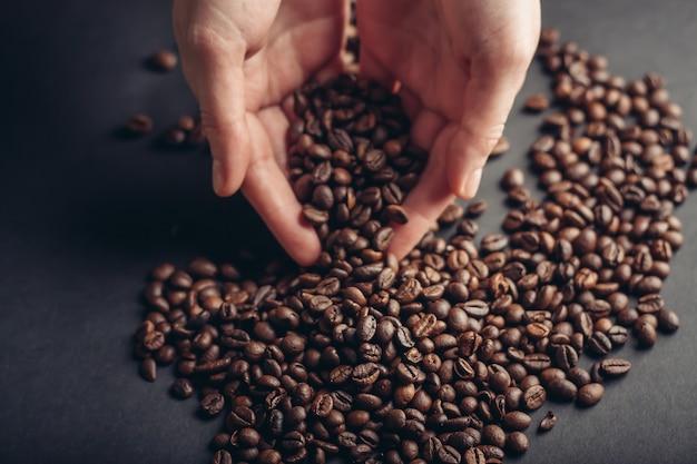 어둠 속에 흩어져있는 손에 커피 콩