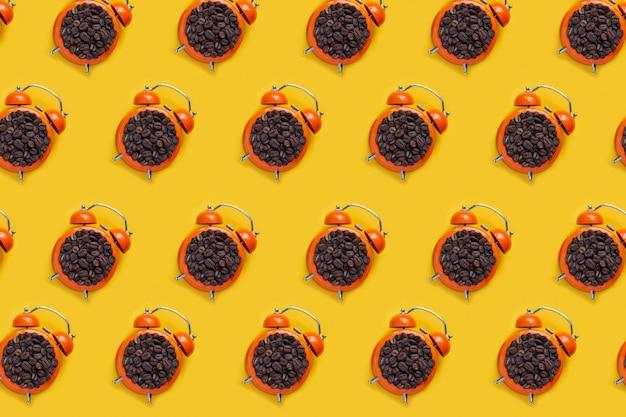 Кофейные зерна в оранжевом будильнике на желтой таблице. выкройка композиции