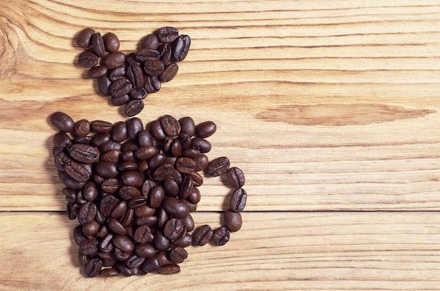 컵 모양의 커피 콩과 나무 배경의 심장, 위쪽 전망. 텍스트를 위한 공간