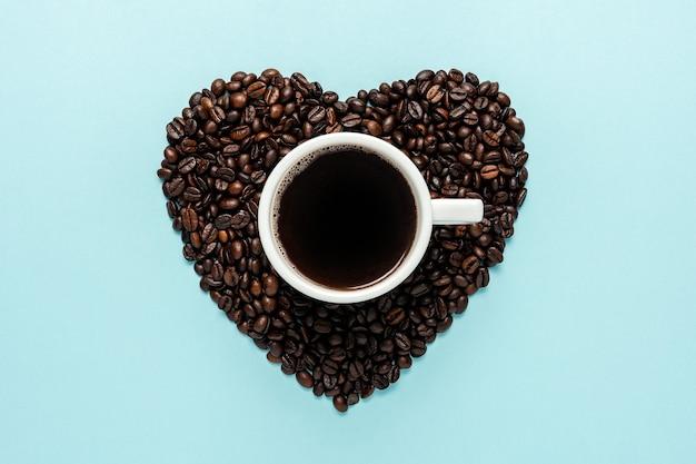 青い背景に白いカップとハートの形のコーヒー豆
