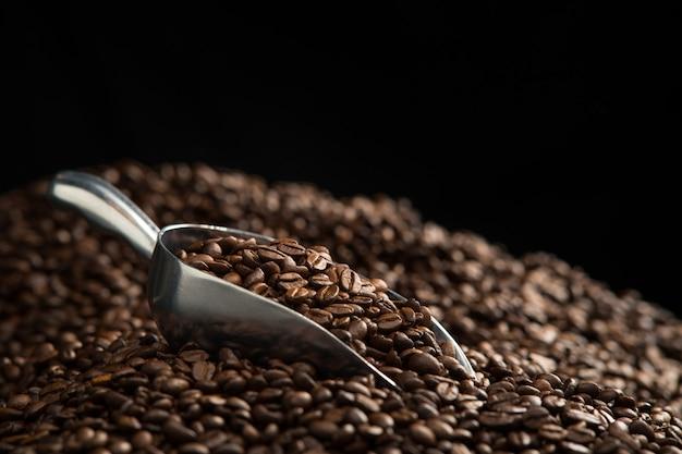 Кофейные зерна в ложке на кучу кофейных зерен на черном фоне