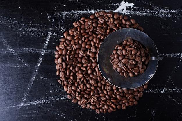 Кофейные зерна в черном блюдце.