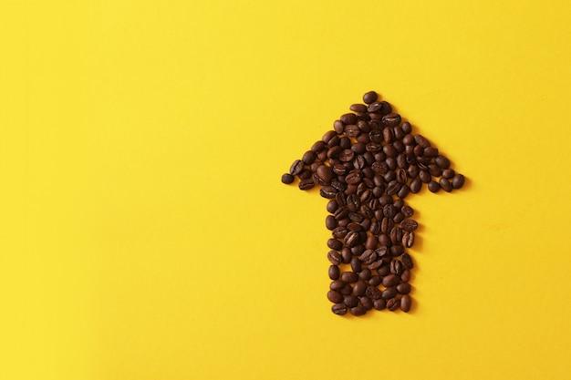 黄色の背景に分離された矢印の形のコーヒー豆。