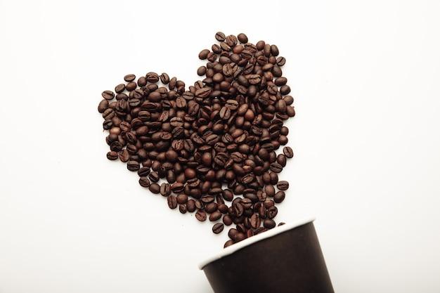 ハートとカップの形のコーヒー豆。
