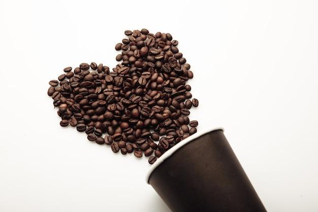 コーヒーカップからハートの形をしたコーヒー豆。