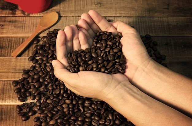 여자의 손에 커피 콩 쇼 사랑