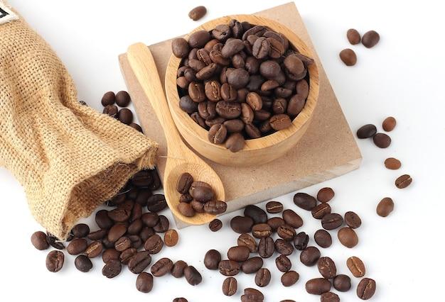 床に散らばっている木製のボウルのコーヒー豆、木のスプーン、白い背景の上のコーヒー袋、上面図。