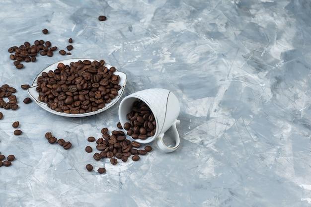 灰色の漆喰の背景に白いカップとプレートのコーヒー豆。ハイアングルビュー。