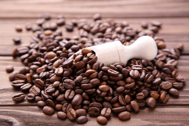 갈색 배경에 나무 숟가락에 커피 콩입니다.