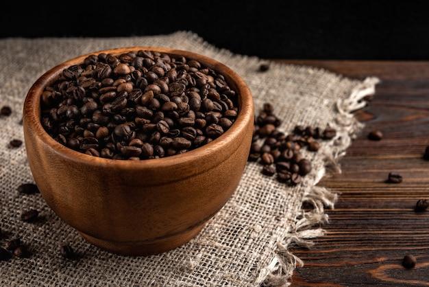어두운 나무 배경에 나무 그릇에 커피 콩.