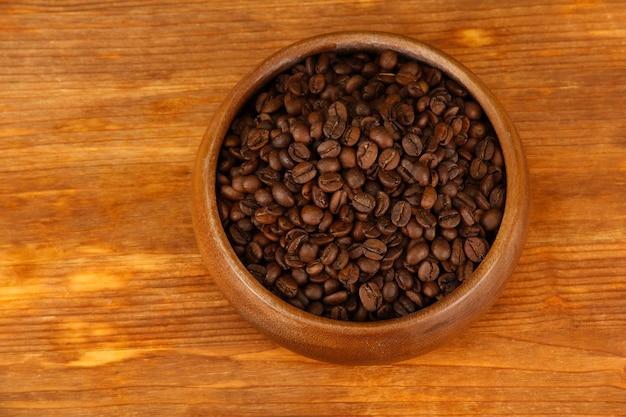 木製のテーブルに木製のボウルにコーヒー豆