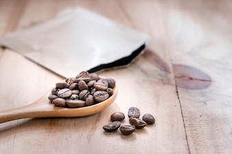 Coffee beans in wooden spoon on wooden table