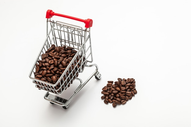白い背景の上の小さなショッピングカート内のコーヒー豆。