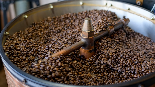 Coffee beans is roasting in roaster machine in coffee shop. Premium Photo