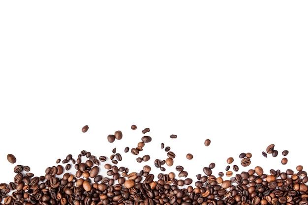 テキスト用のコピースペースで白い壁に分離されたコーヒー豆。コーヒーの壁やテクスチャの概念。