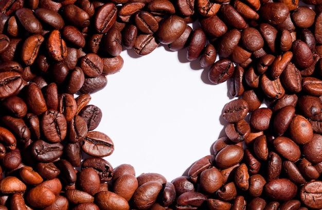 Кофейные зерна, изолированные с белым столом, центральный круг
