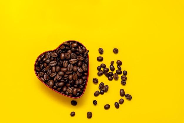 Кофейные зерна в форме сердца на желтом
