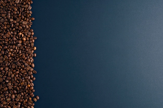 Coffee beans on left on black background