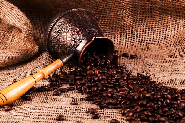 Coffee beans lie in cezve on the hessian