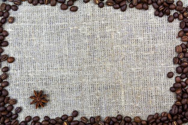 Coffee beans lie on a linen cloth burlap. retro background