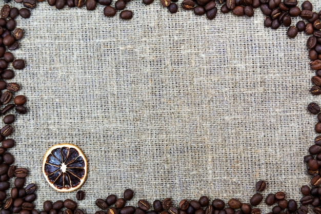 Coffee beans lie on a linen cloth burlap. retro background
