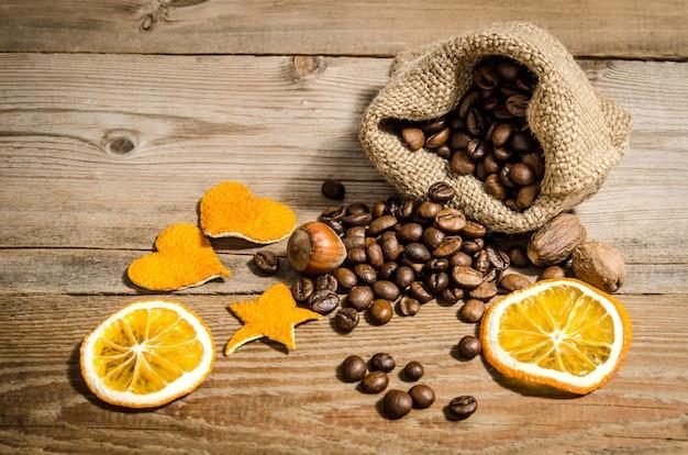 木製のテーブルにオレンジの皮から作られたコーヒー豆、ナッツ、フィギュア