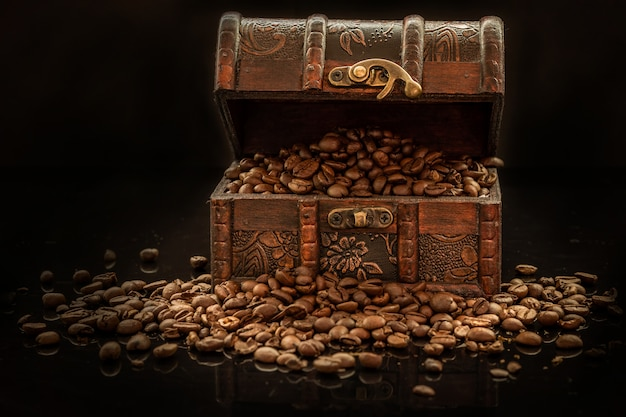 Coffee beans and old treasure chest on black background - the black gold
