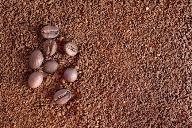 挽いたコーヒー、コーヒーパウダーを背景にしたコーヒー豆