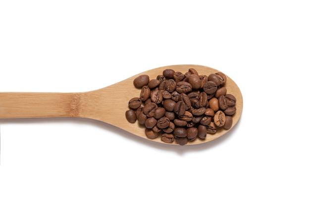 Кофейные зерна на деревянной ложке на белом фоне вид сверху