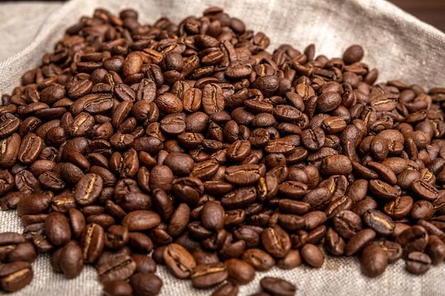 Кофейные зерна на деревянном столе на черном. вид сверху.