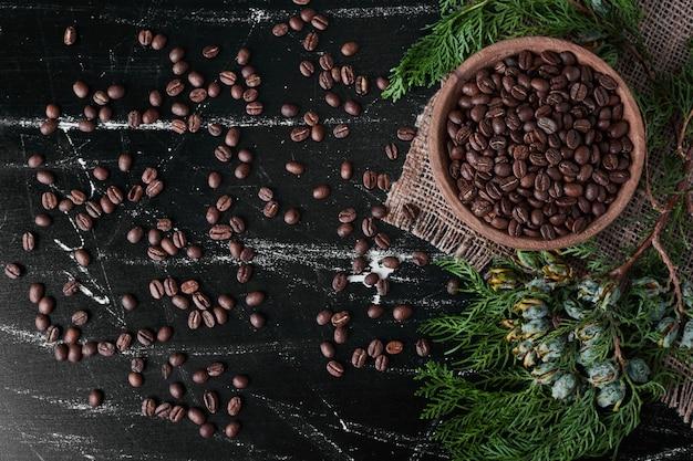 Кофейные зерна на черном фоне в деревянной чашке.